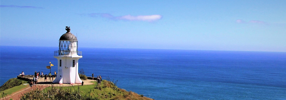 The Cape Reinga Lighthouse over looking the ocean with a blue sky