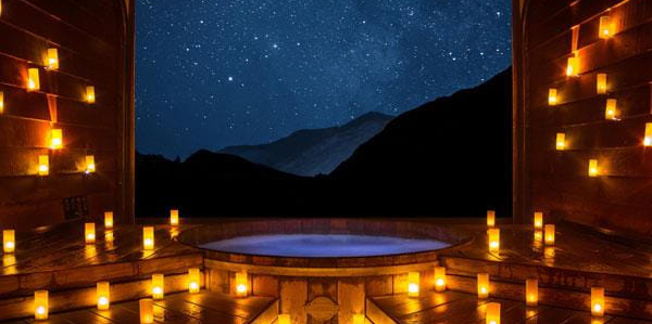 Hot pools at night with candles overlooking mountains