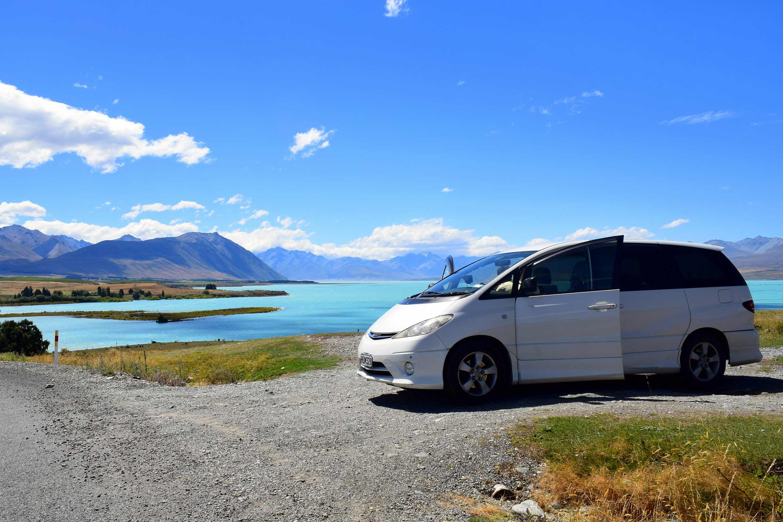 Campervan in front of a lake front overlooking lakes and mountains in New Zealand.