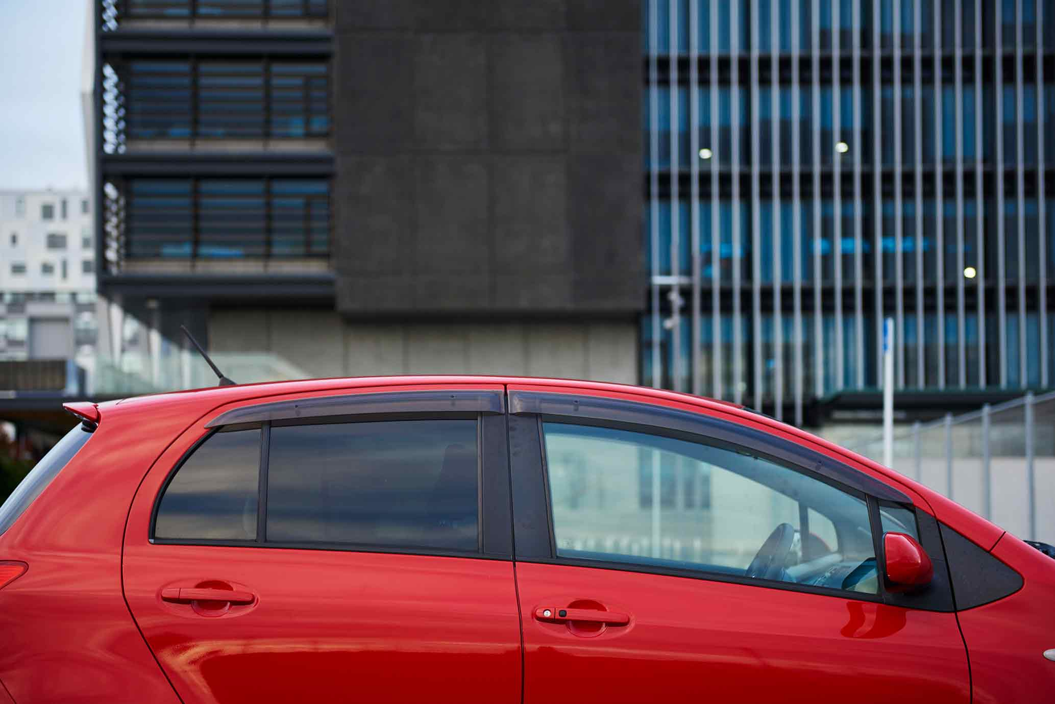 Red sedan car rental by an office building