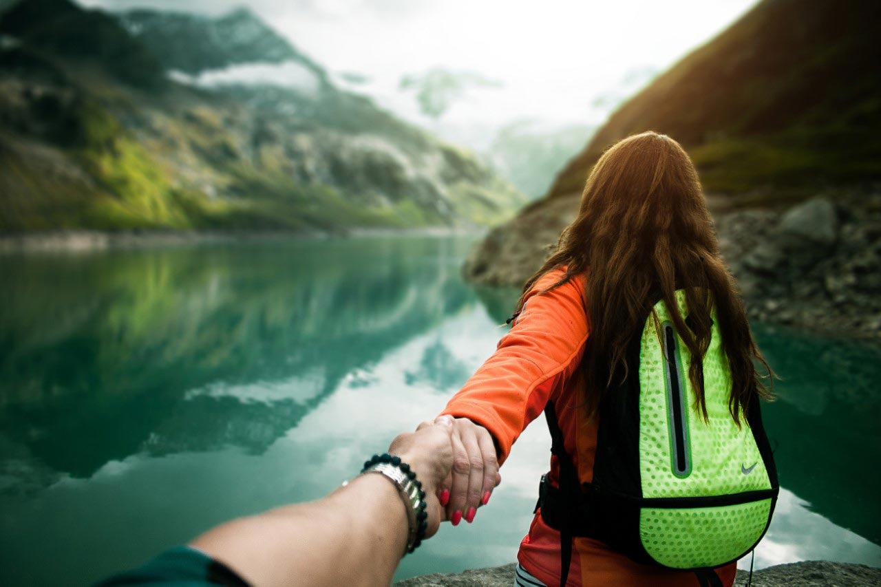 Holding woman's hand by water and mountains in New Zealand