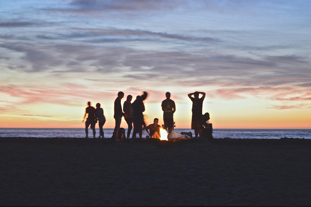 Group of friends around a sunset bonfire at the beach