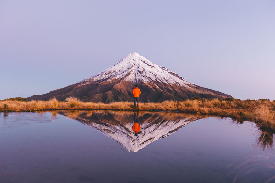 Man standing by NZ snow-capped Mount Taranaki and lake