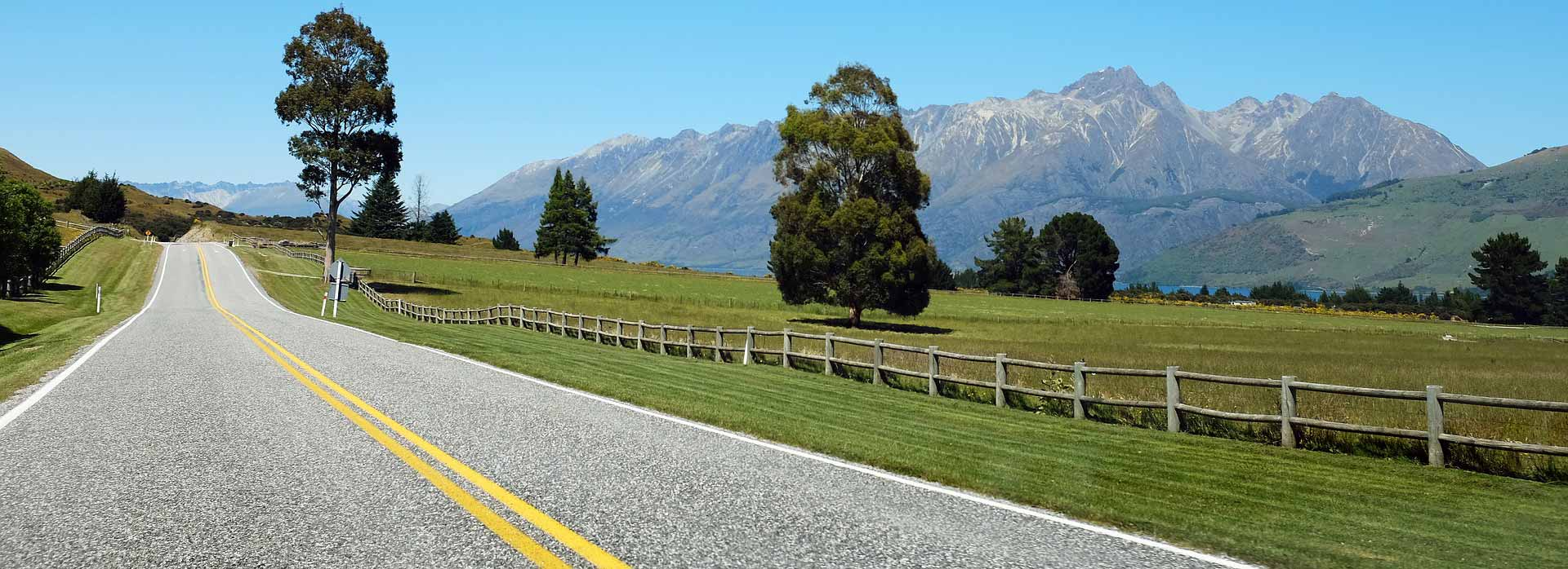 New Zealand country road with farm fences and mountains