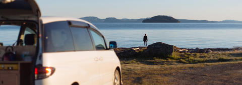 Mode Campervan with person standing next to a lake