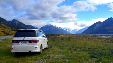 Mode Campervan parked in a field with mountains