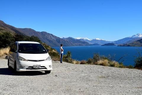 Mode Camper parked while person overlooks lake and mountains