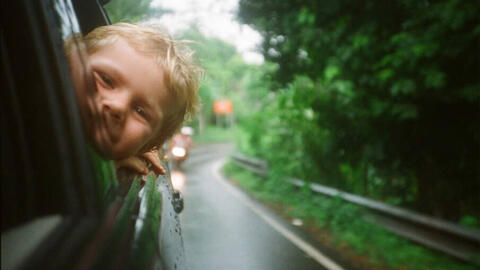 Child with head out car window
