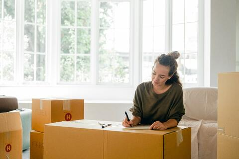 Woman writing on a cardboard moving box in a living room