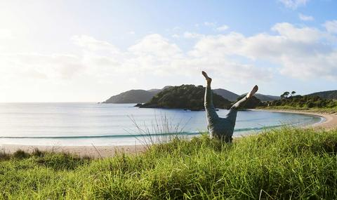 Person doing a headstand in the grass at the beach