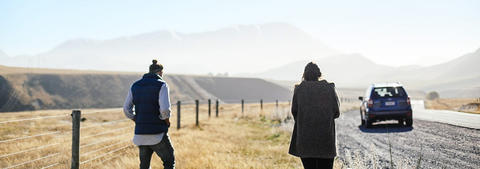Couple walking on grass verge of a gravel road