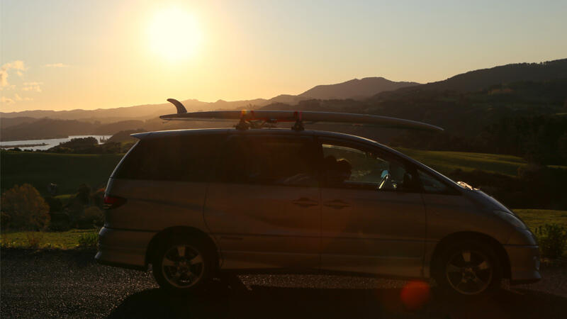 Campervan with surfboard on the roof, sunset and rolling hills in the background