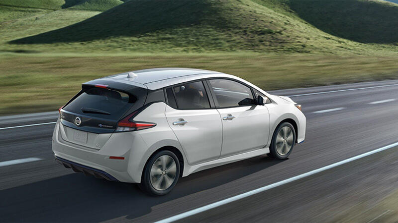 White Nissan Leaf driving past green hills