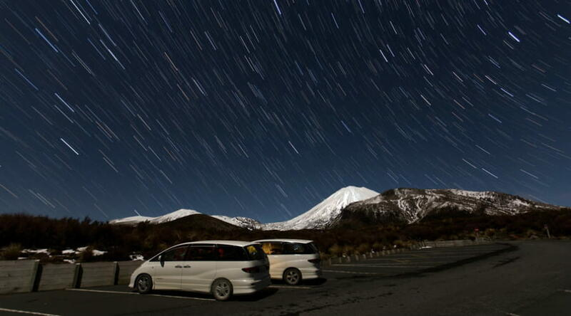Two mode campervans parked on a snowy mountain at night