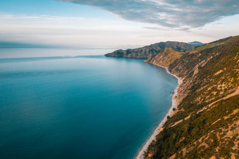 Aerial shot of a calm blue ocean along a peninsula