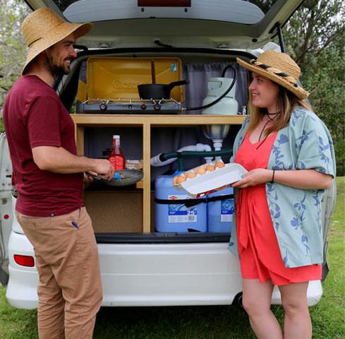 Couple cooking breakfast from self-contained campervan kitchen